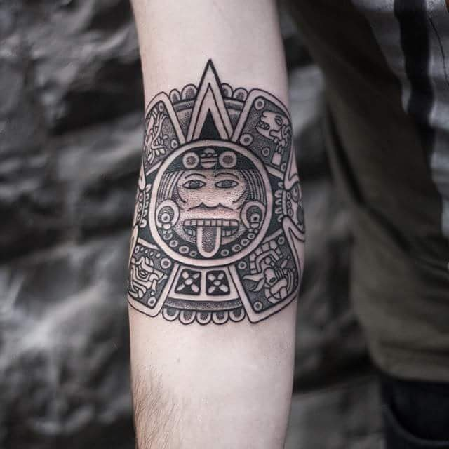 Typical black ink forearm tattoo of Mayan tablet