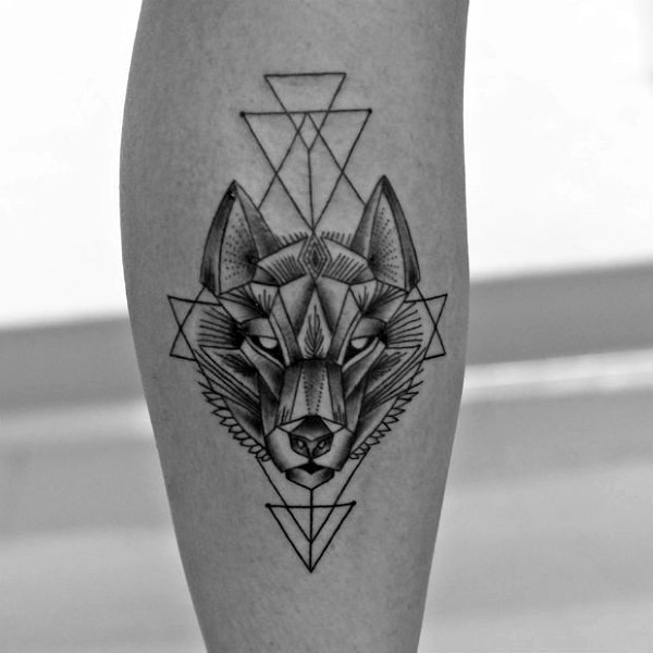 Typical black ink leg tattoo of wolf head with geometrical ornaments