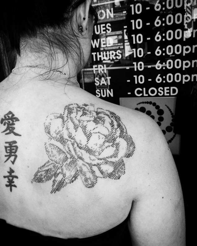 Typical black ink linework style scapular tattoo of big rose