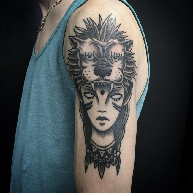 Typical black ink shoulder tattoo of woman face with lion skin helemet