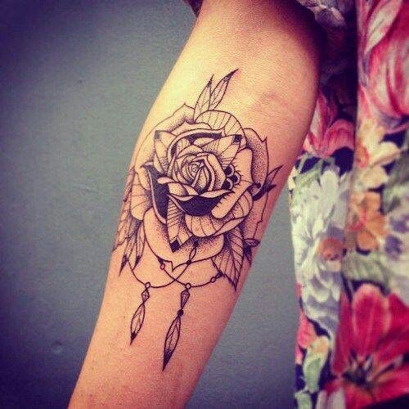 Typical black ink vintage style forearm tattoo of rose flower