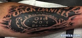 Typical blackwork style arm tattoo of Jack Daniels bottle lettering