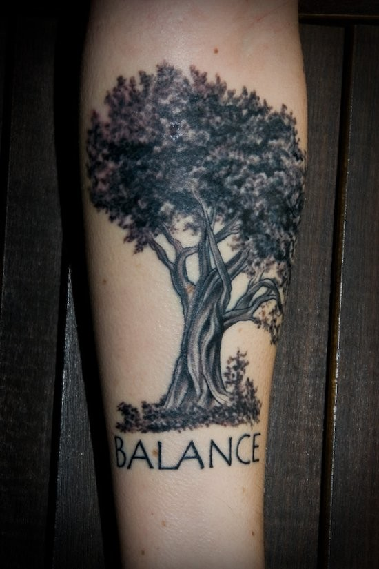 Typical colored forearm tattoo of big tree stylized with lettering