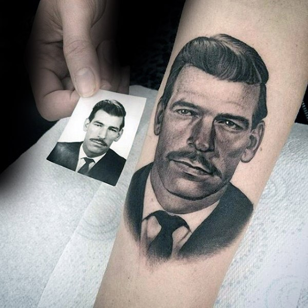 Typical colored portrait style forearm tattoo of man face