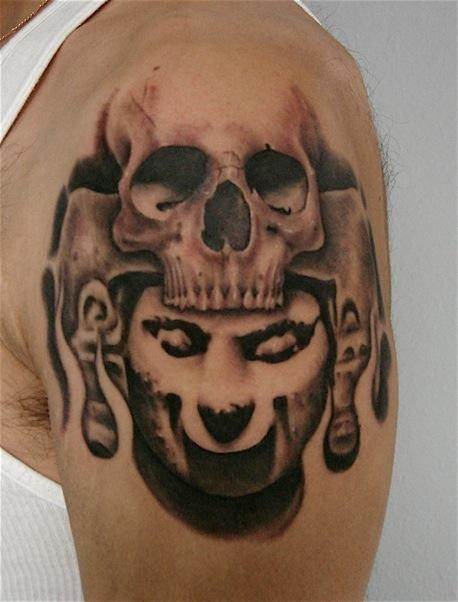 Typical colored shoulder tattoo of human skull and stone statue