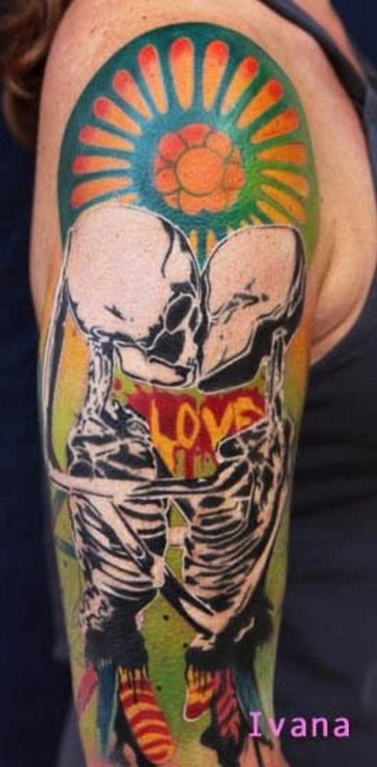 Typical colored shoulder tattoo of kissing skeleton couple