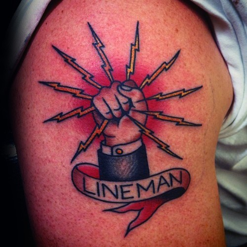 Typical colored shoulder tattoo of lineman symbol with lettering