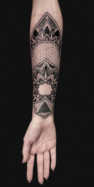 Typical dotwork style forearm tattoo of floral ornament