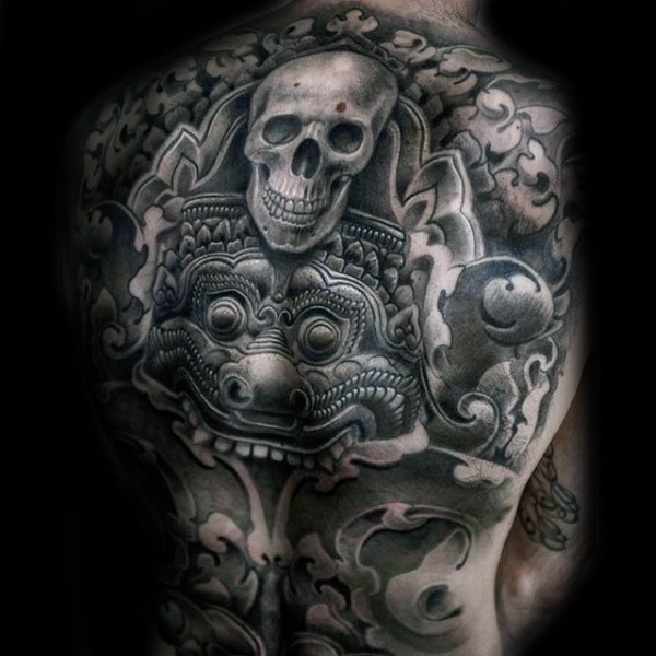 Typical gray washed style human skull tattoo on whole back combined with Aztec tablet