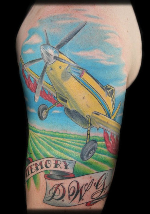 Typical illustrative style shoulder tattoo of little plane with lettering