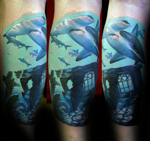 Typical multicolored leg tattoo of hammer sharks and underwater ruins