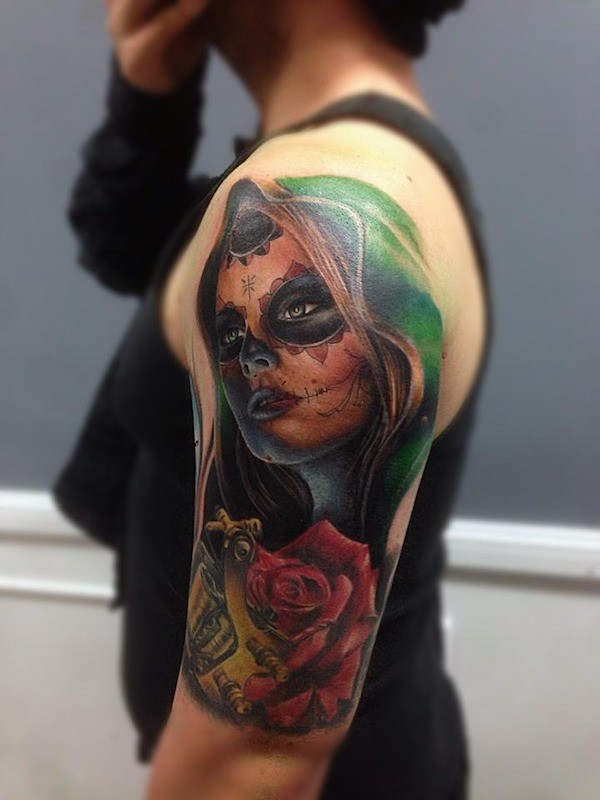 Typical multicolored shoulder tattoo of Mexican woman portrait and flower