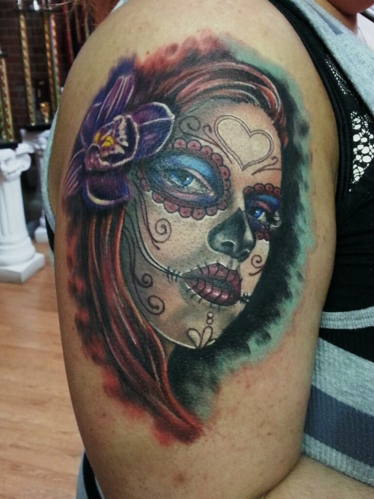 Typical multicolored shoulder tattoo of woman portrait and flower in hair