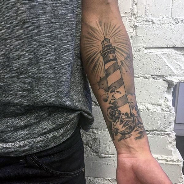 Typical new school style black and white lighthouse with waves tattoo on forearm