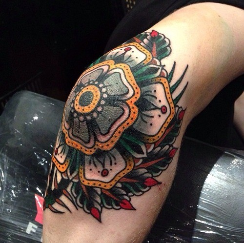 Typical old school style knee tattoo of plane with flowers
