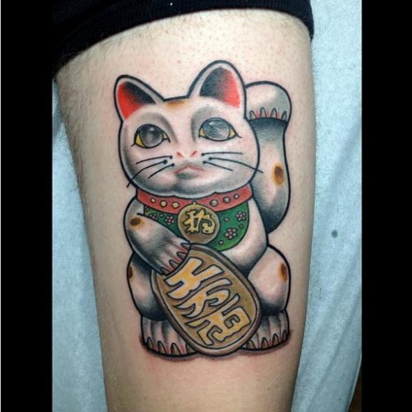 Typical painted and colored thigh tattoo of maneki neko japanese lucky cat with necklace