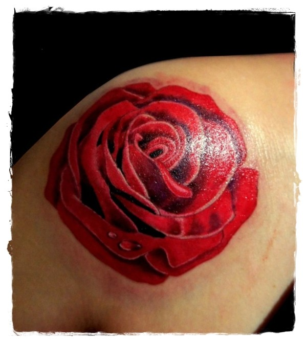 Typical painted red colored rose tattoo on shoulder
