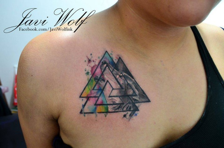 Typical watercolor style small mystic symbol tattoo on chest