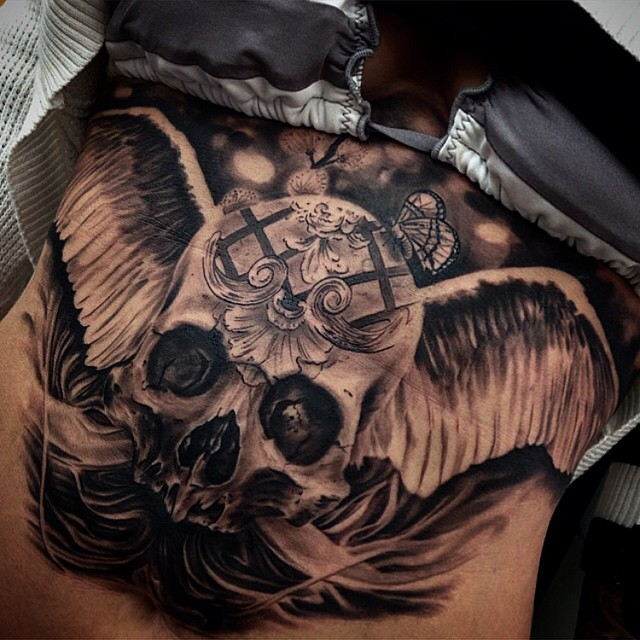 Unbelievable mysterious human skull with wings tattoo combined with tiny butterfly