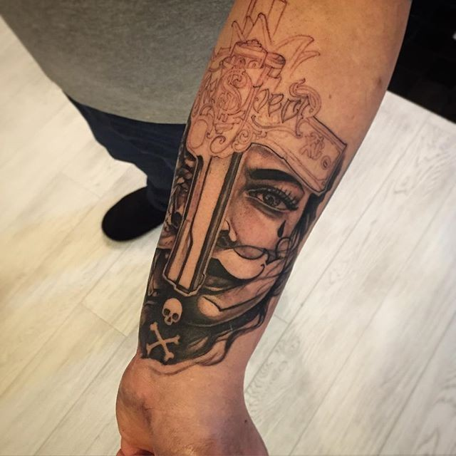 Unfinished black ink forearm tattoo of mans face with pistol