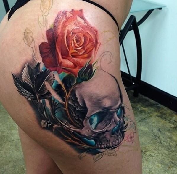 Unfinished colored thigh tattoo of magical human skull with rose