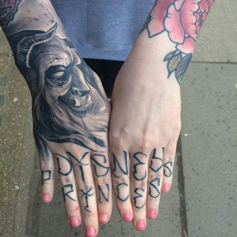 Unique black and white fantasy monster face tattoo on hand combined with lettering