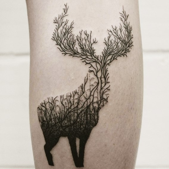 Unique black ink deer shaped tattoo stylized with forest trees