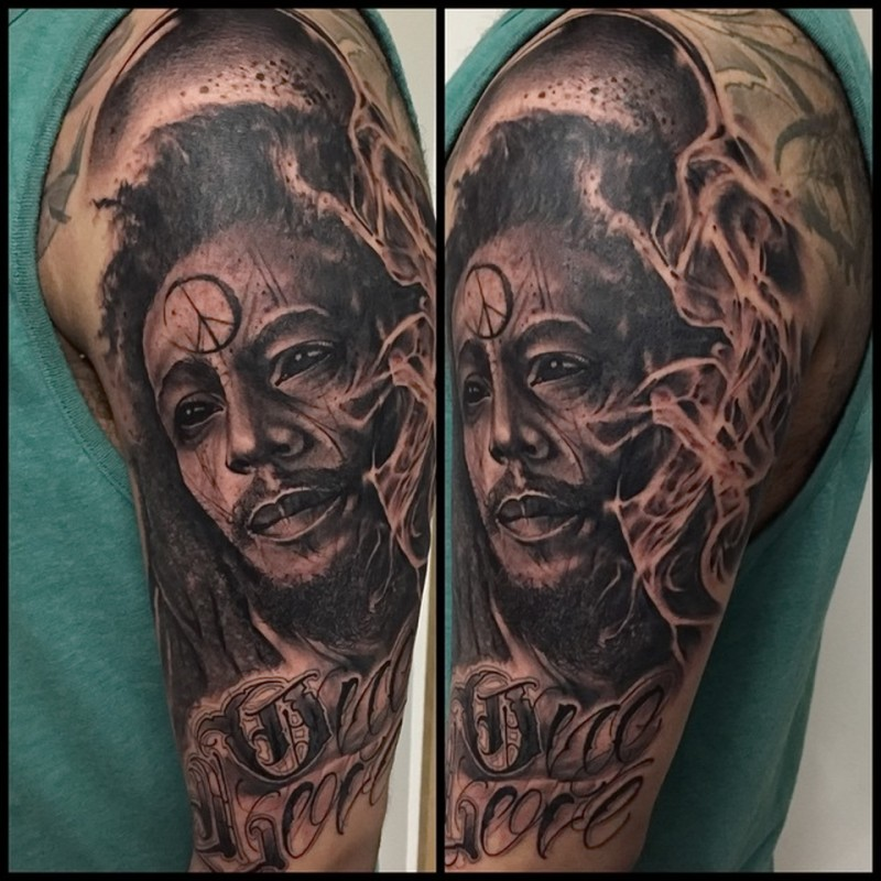 Unique black ink shoulder tattoo of famous man with lettering