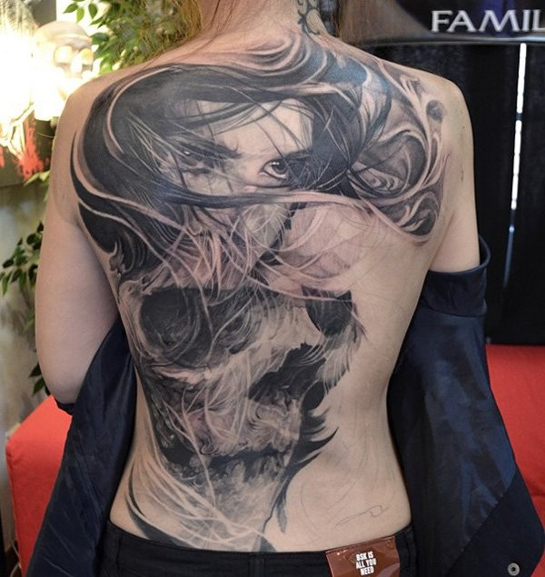 Unique combined massive black ink skull tattoo on back with woman portrait