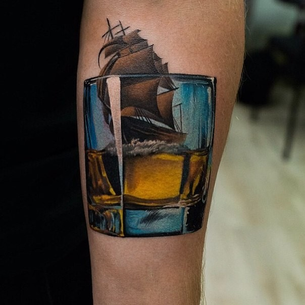 Unique designed 3D like colored whiskey glass tattoo on forearm stylized with sailing ship