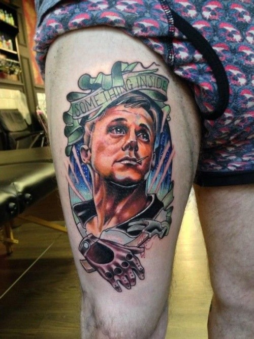 Unique designed colorful man portrait tattoo on thigh with lettering