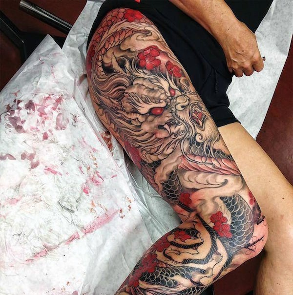 Unique designed colorful massive on whole leg tattoo of Asian dragon with flowers
