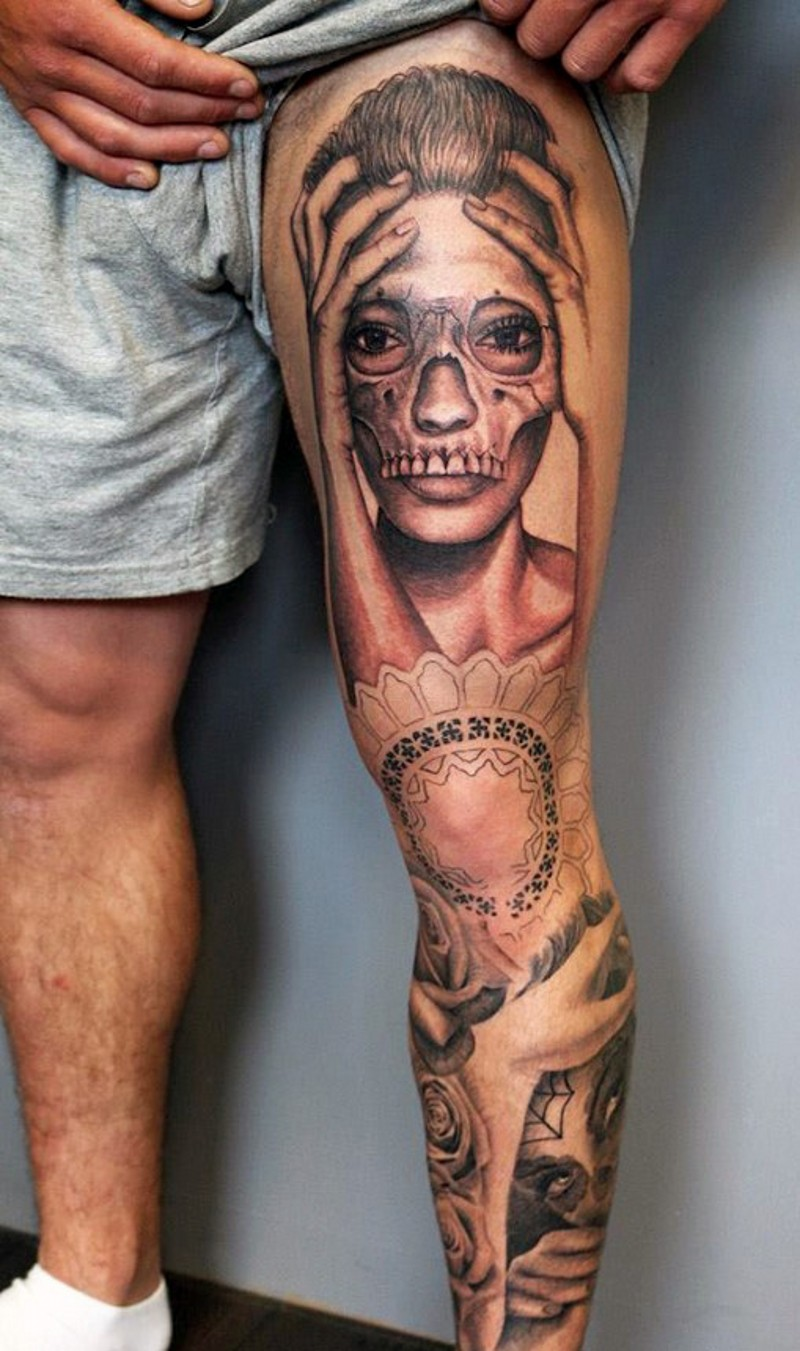 Unique painted black and white woman portrait with skull shaped mask tattoo on thigh