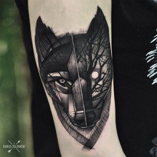 Unique painted black ink wolf face tattoo on forearm stylized with night forest