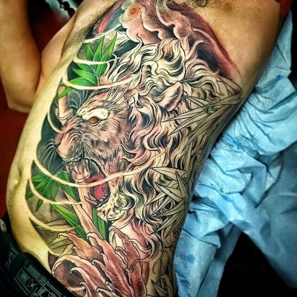 Unique style half colored lion in jungle tattoo on side