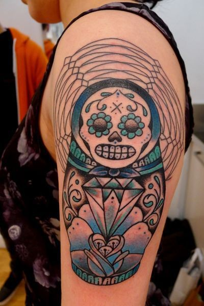 Illustrative style colored shoulder tattoo of creepy Matryoska doll with jewelry