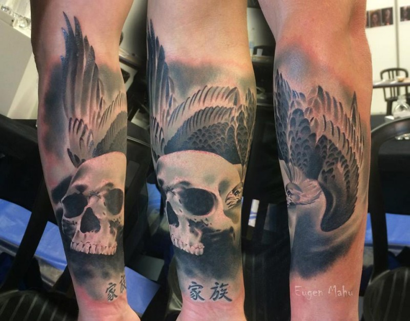 New school style colored forearm tattoo of human skull with bird and symbols