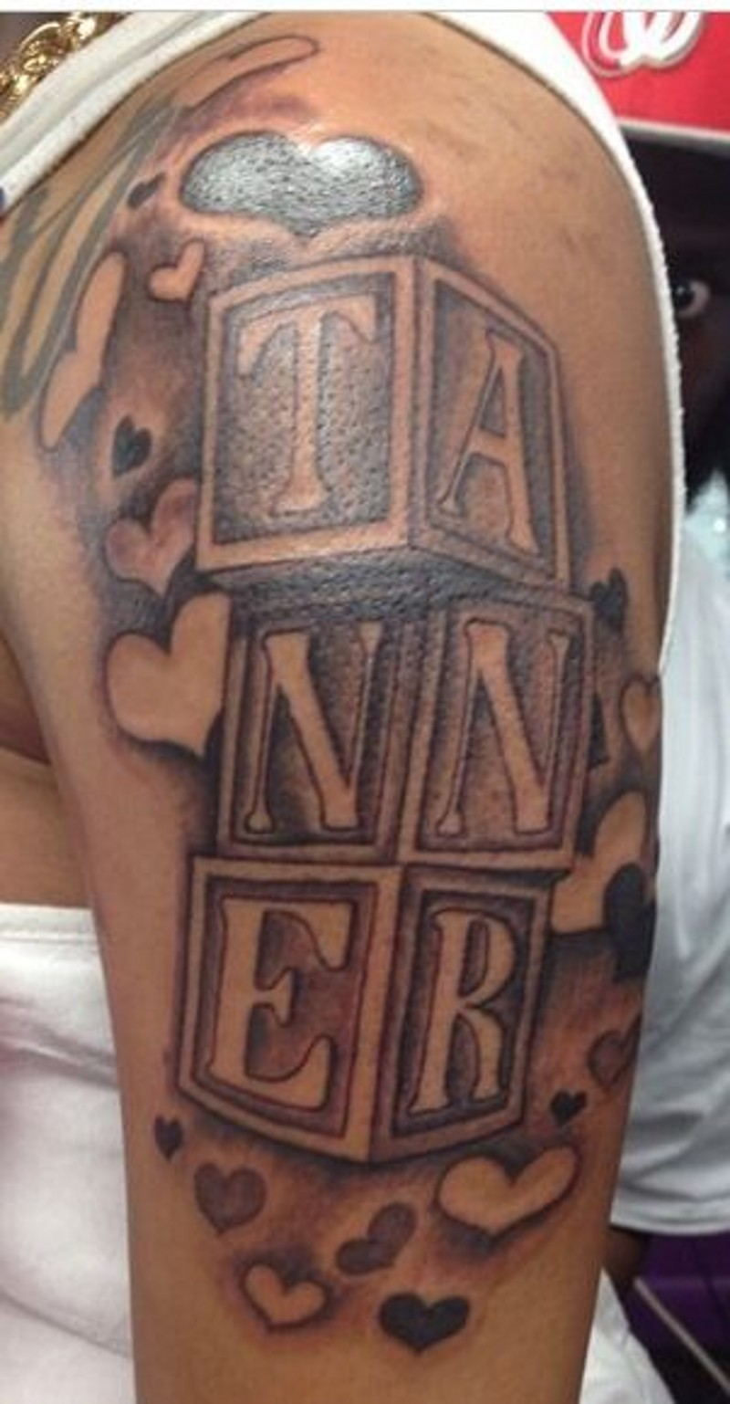Unusual black ink big cubes with letters tattoo on shoulder stylized with hearts