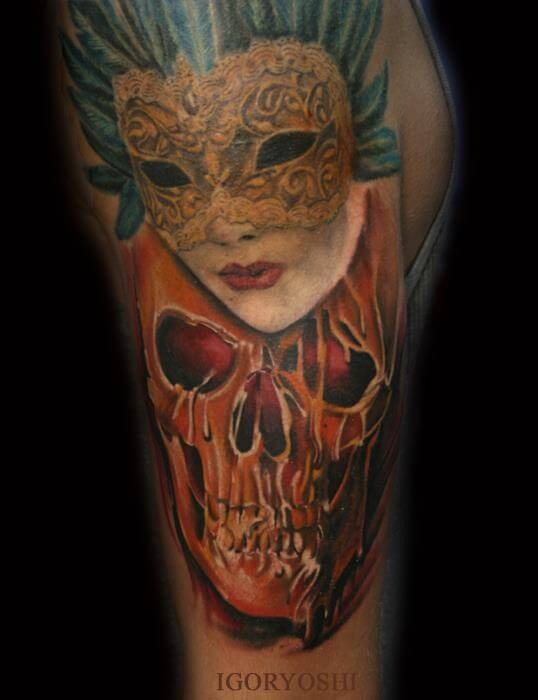 Unusual colored detailed human skull tattoo on shoulder combined with masked woman