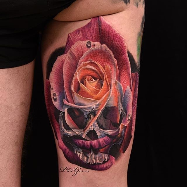 Unusual combined and colored thigh tattoo of rose with human skull