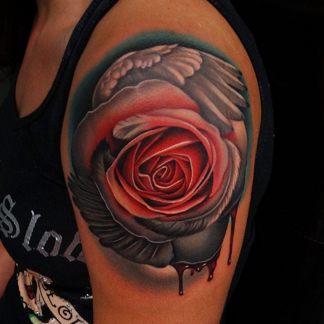 Unusual combined big bloody colored rose with angel wing tattoo on shoulder