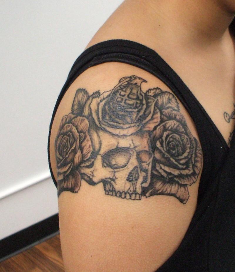 insolito combinazione grande cranio con fiore e bomba a mano tatuaggio su spalla