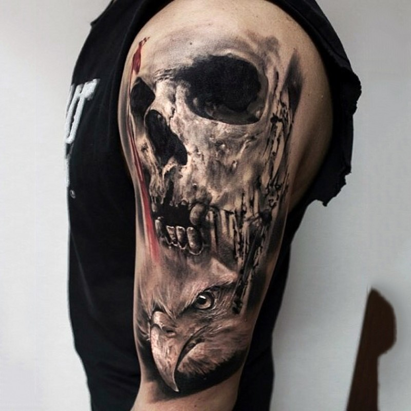 Unusual combined black and white detailed human skull tattoo on shoulder with eagle head