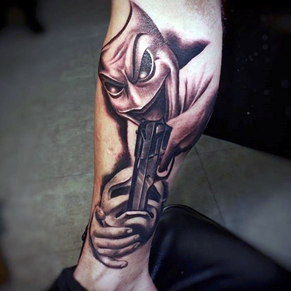 Unusual designed and colored leg tattoo of happy mask with pistol combined with sad mask