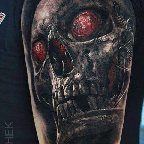 Unusual designed by Eliot Kohek upper arm tattoo of skull with bloody eyes