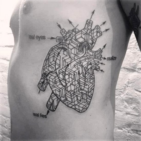 Unusual looking black ink side tattoo of human heart with schematics and lettering