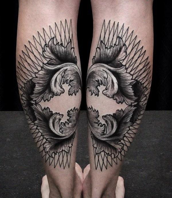 Unusual tribla style black ink partial tattoo on legs