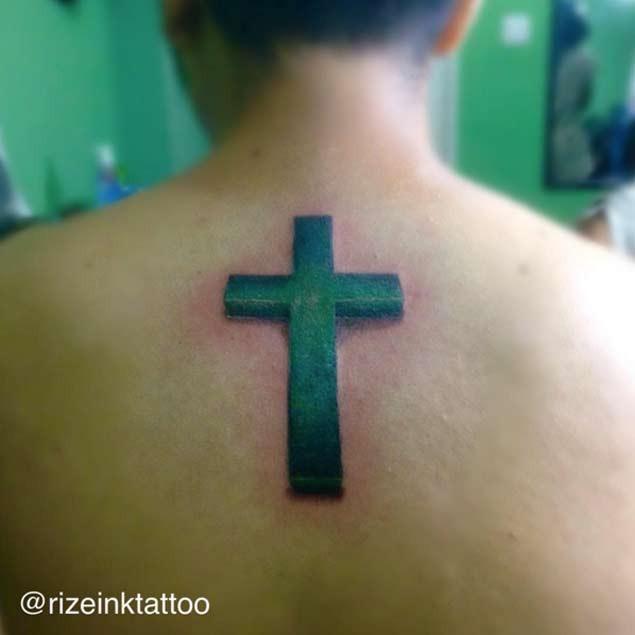Upper back 3D realistic green colored cross tattoo