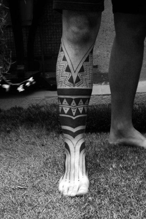 Usual accurate painted black ink tribal paintings tattoo on leg and foot area