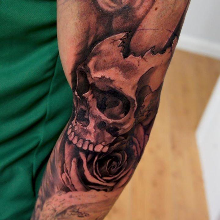 Usual black ink broken human skull tattoo on half sleeve with rose